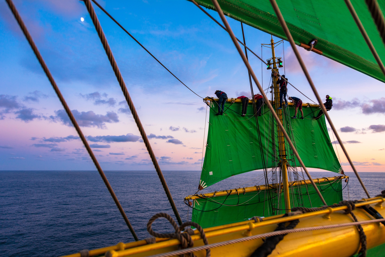 ship with green sail on sea