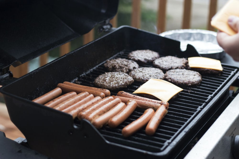 person standing in front grill grilling sausage