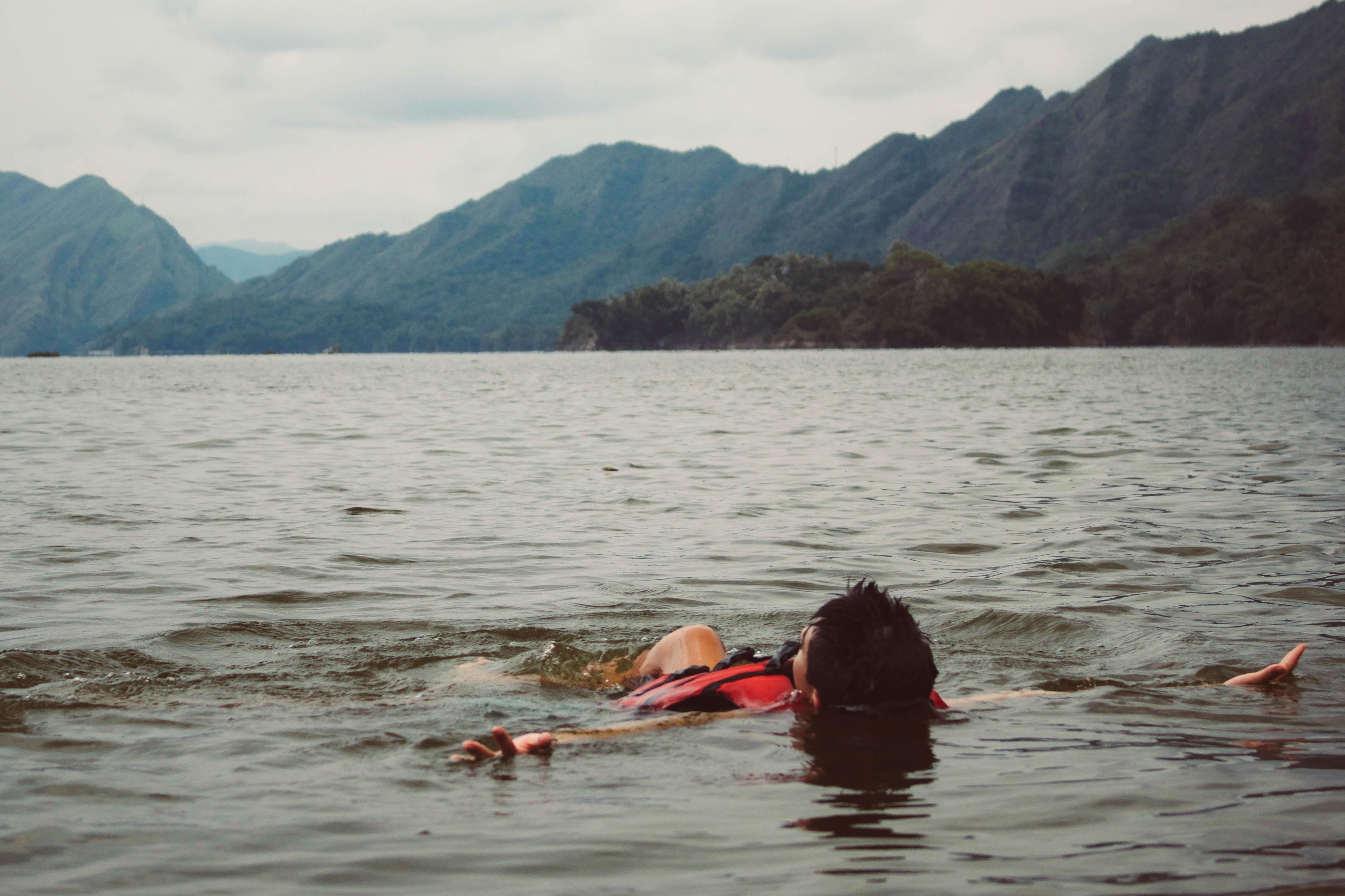 man floating on lake under dark sky