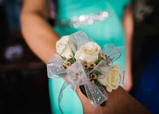selective focus photography of woman's wrist wearing corsafge