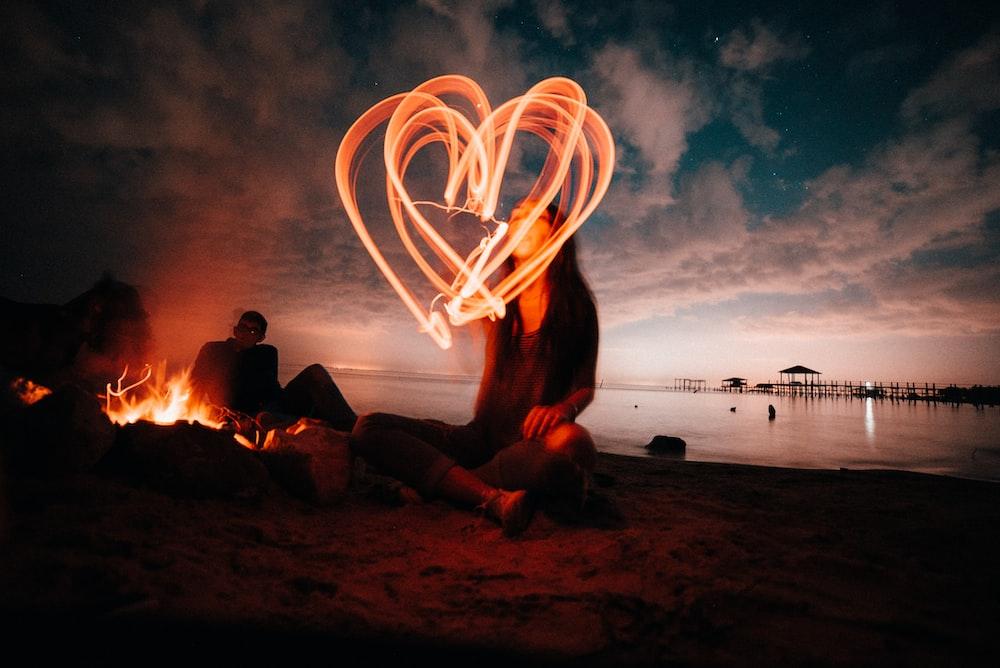 woman sitting on sand near bonfire