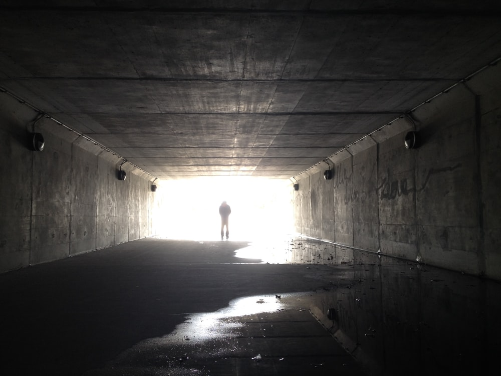 person walking in tunnel