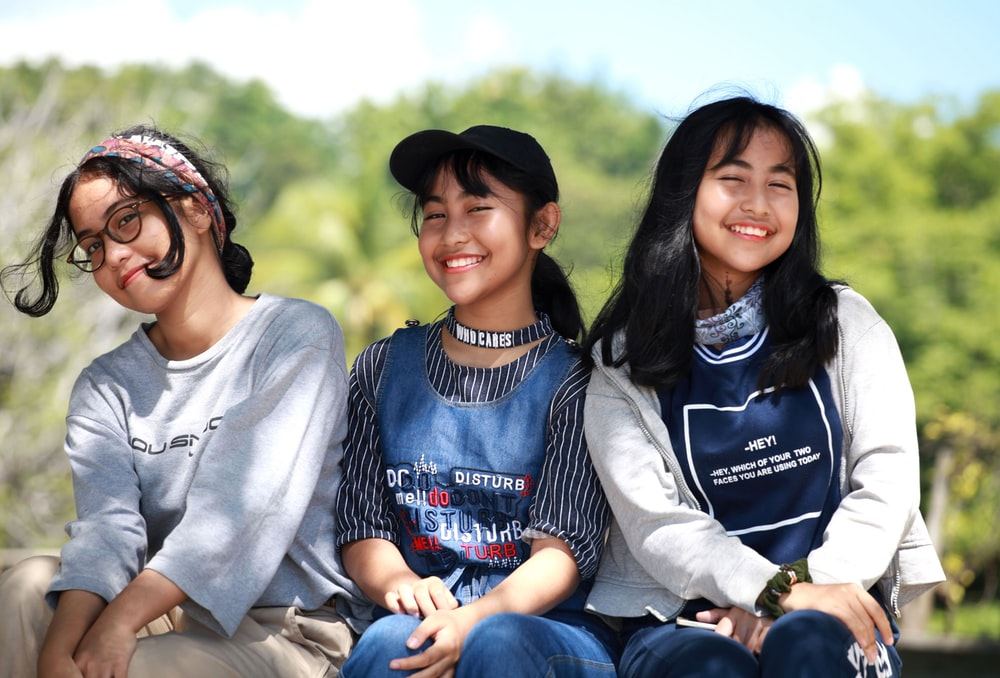 three women sitting near trees