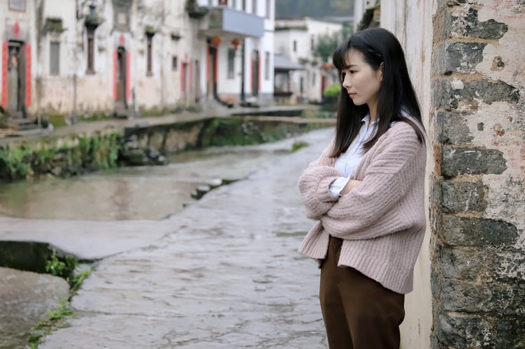 A photo of a young woman standing alone on the side of a street, staring forward. It looks like she may be in a dark place, mentally.