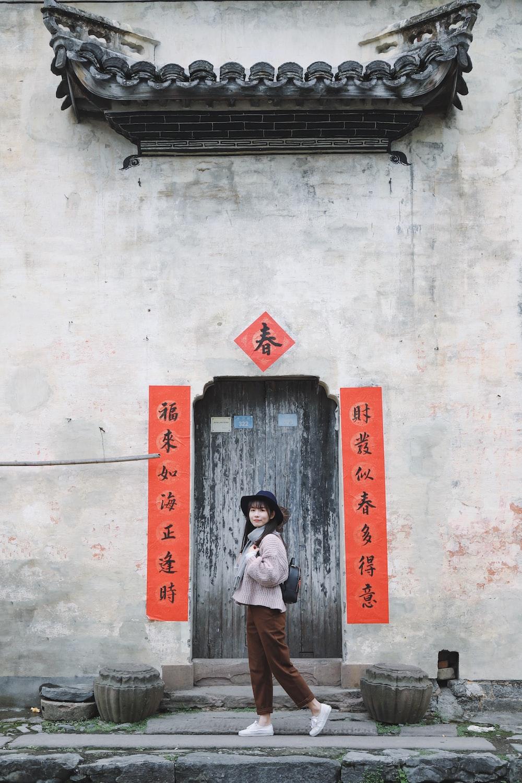 standing woman in front of closed door