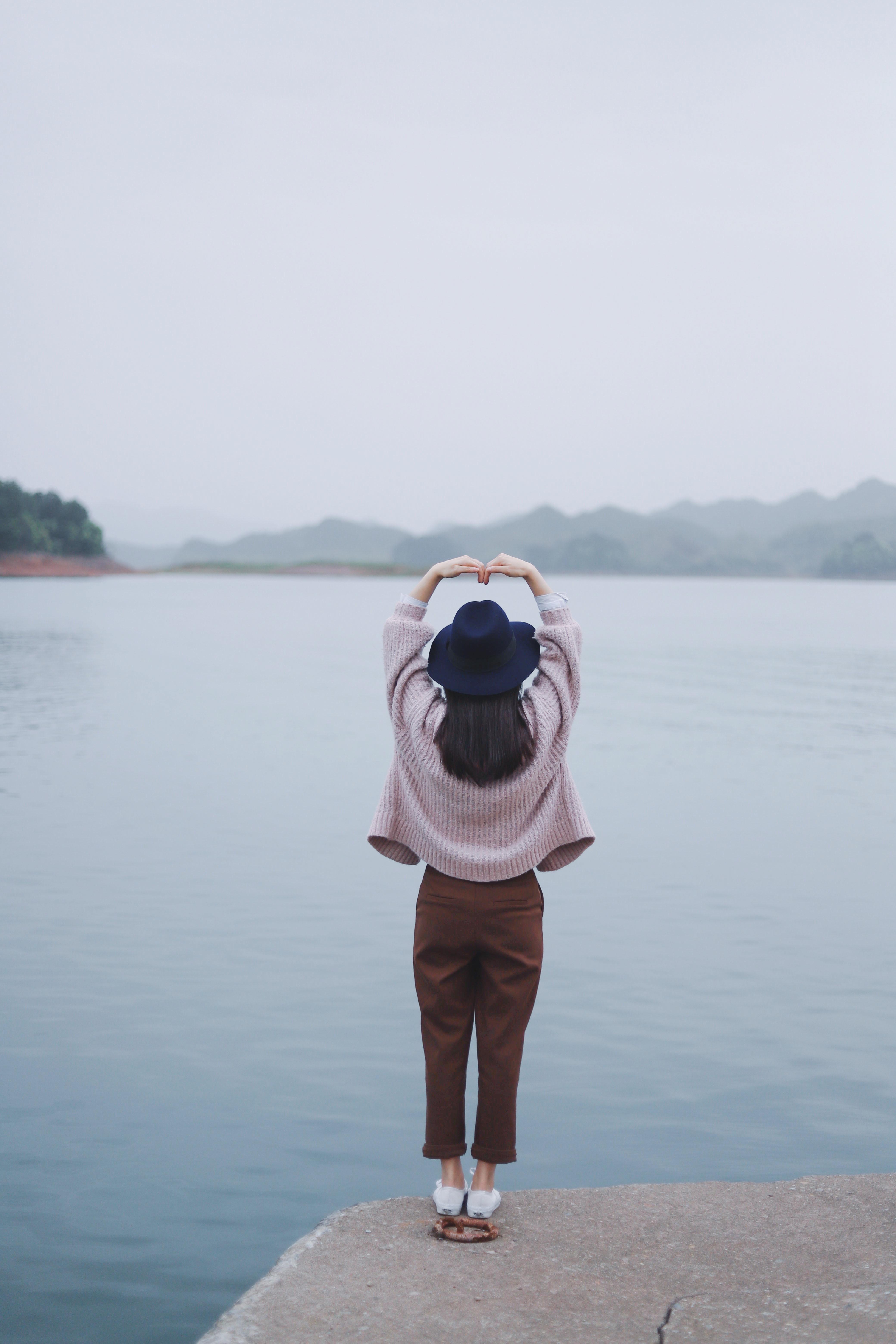 woman taking a heart pose beside body of water