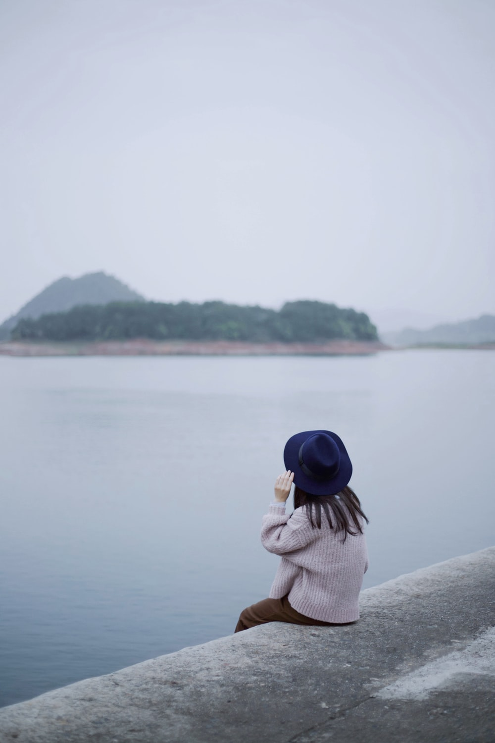 woman sitting on concrete edge in front of body of water
