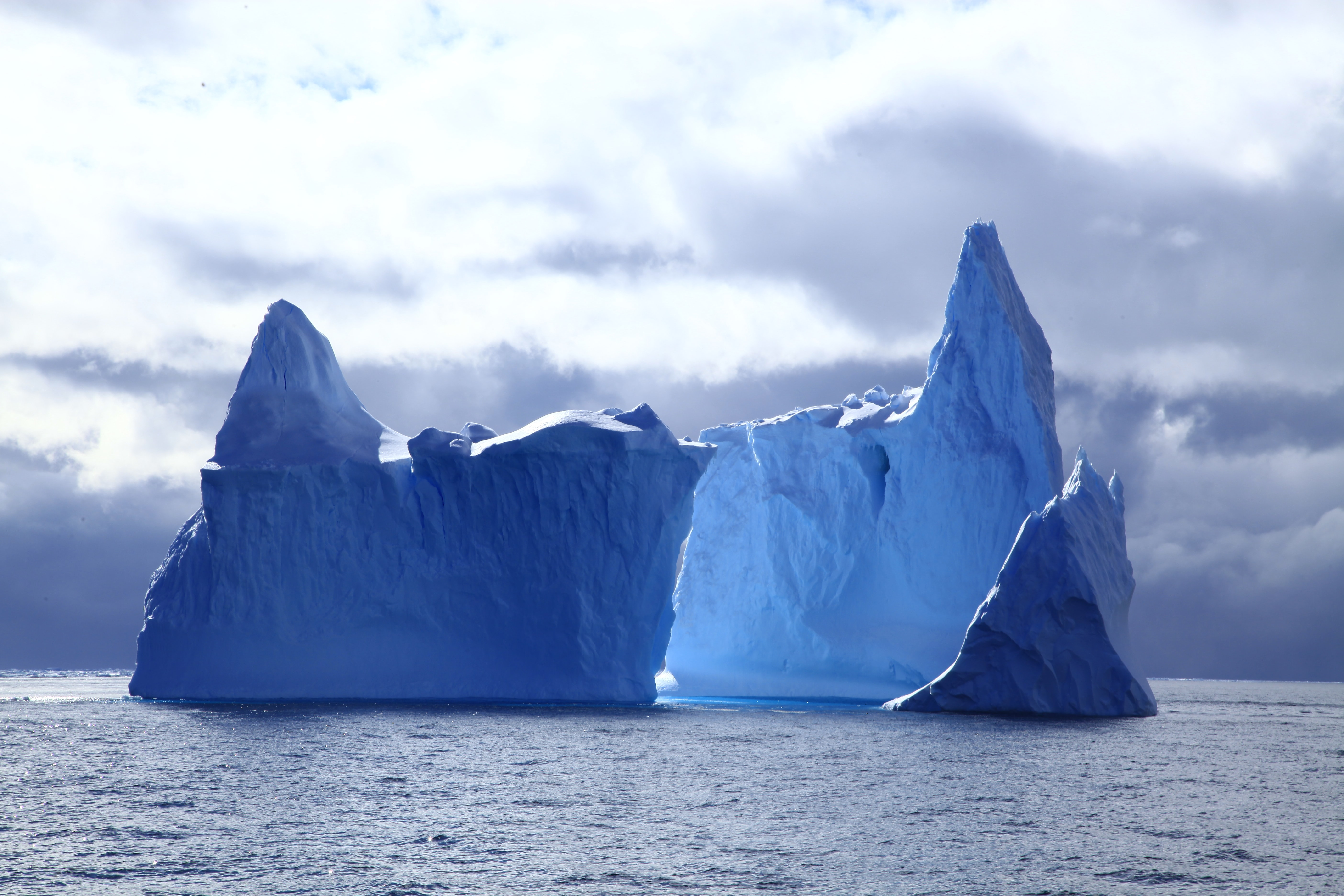two icebergs under cloudy sky at daytime
