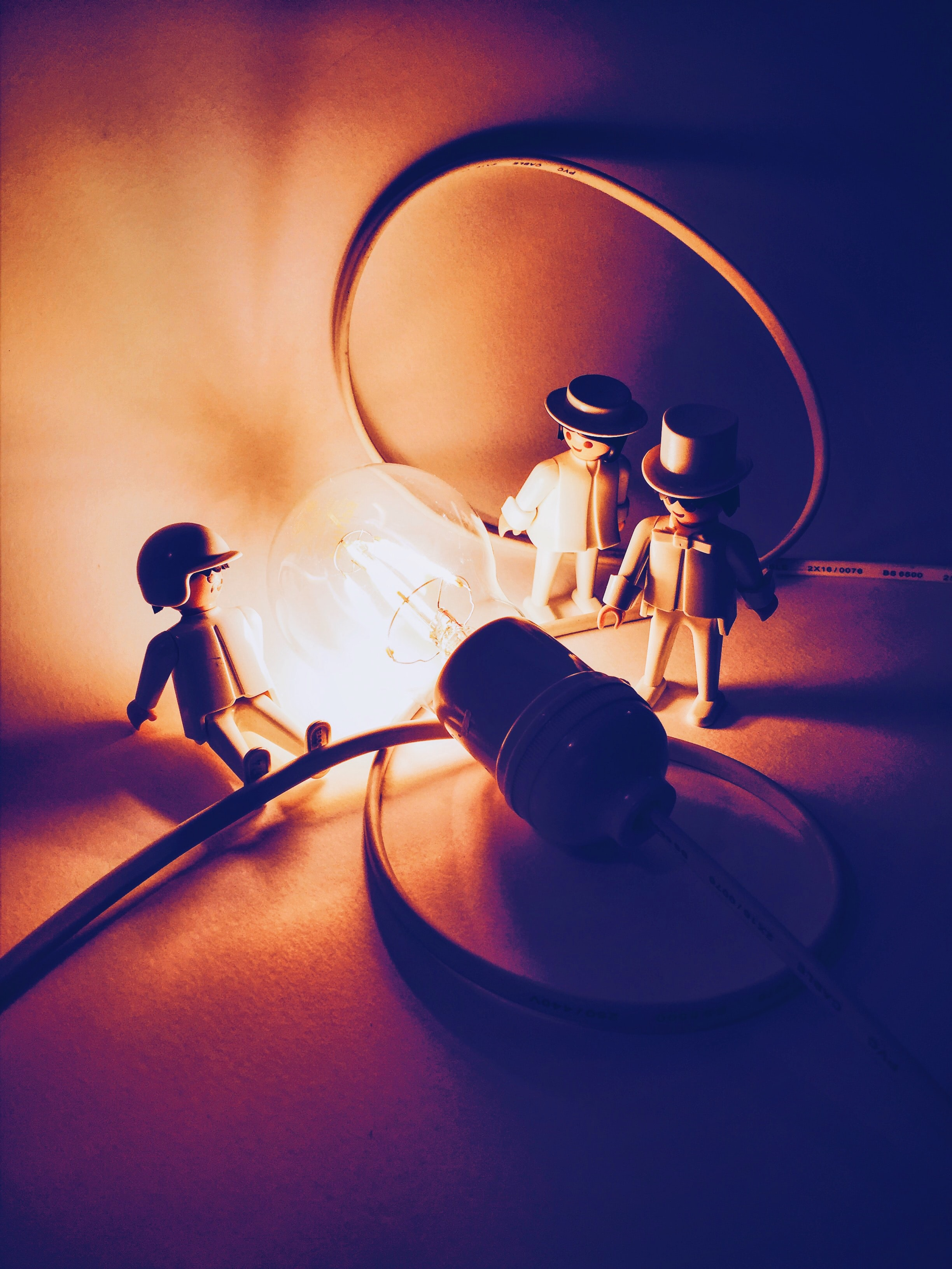 selective focus photography of three men figurines near lighted light bulb