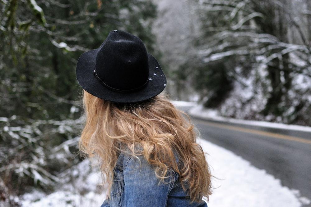 woman wearing blue denim jacket and black cowboy hat near road