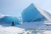 person riding bicycle throught ice ridges
