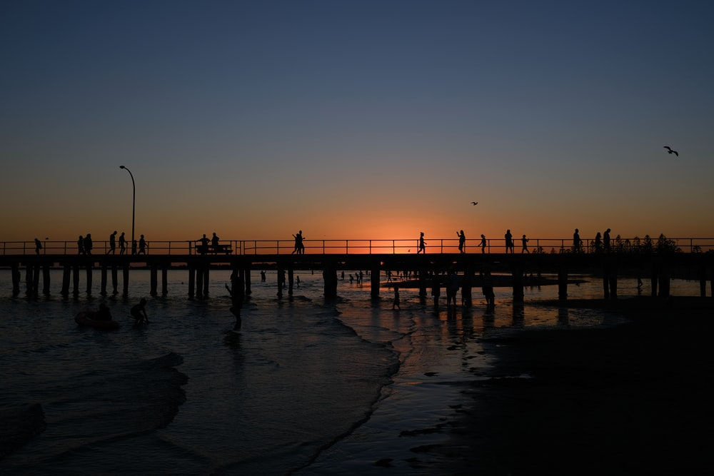 silhouette of people on bridge during sunset
