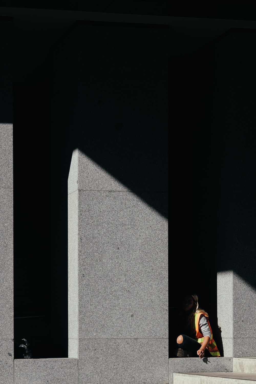 person sitting along pillars on hallway
