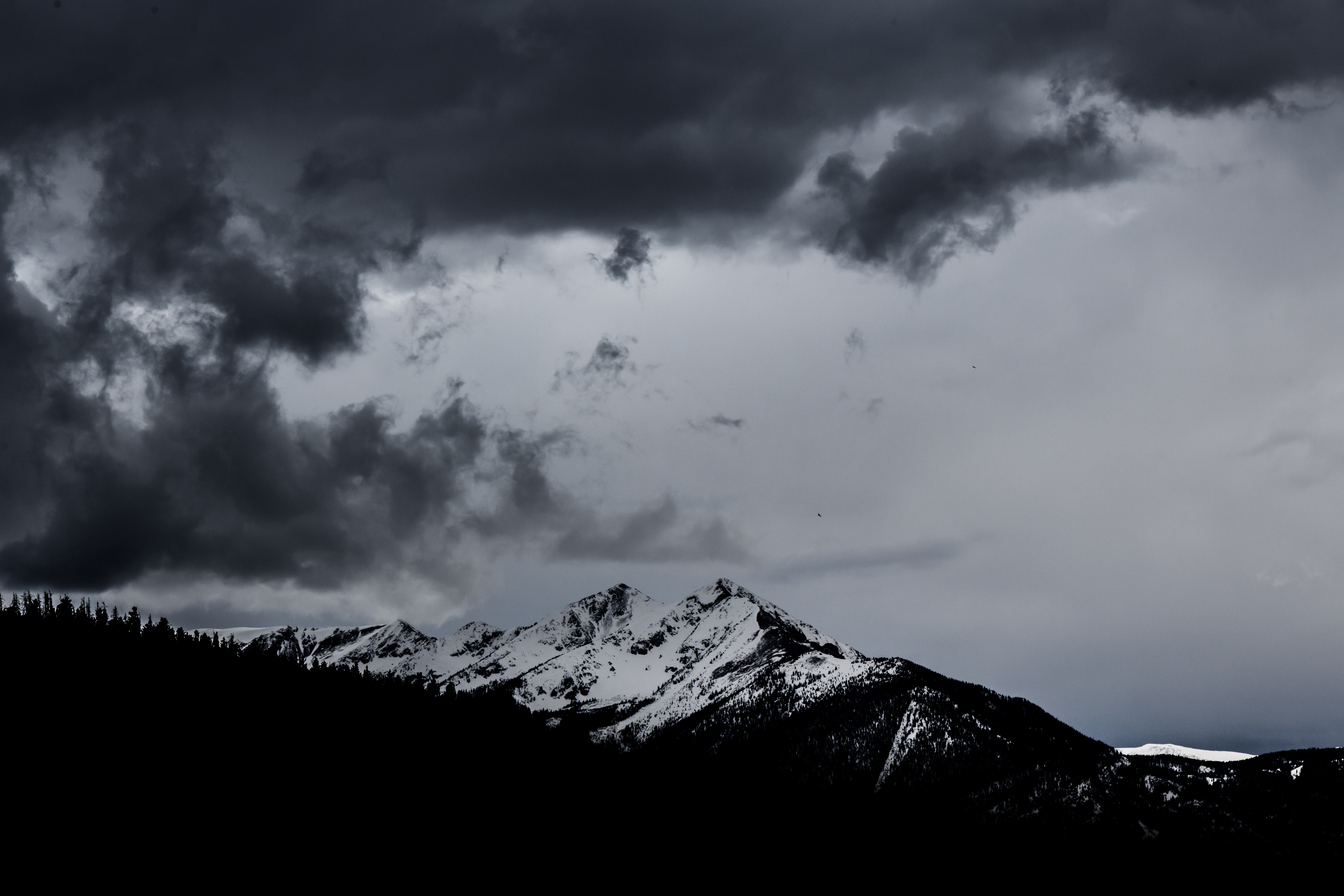 snowy mountain under dramatic clouds