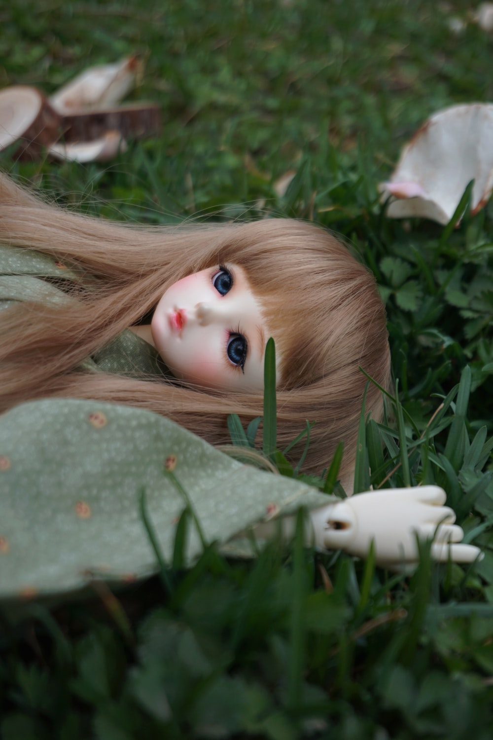 female doll in green dress laying on grass field