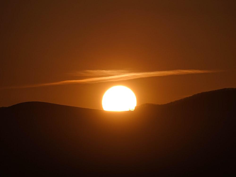 silhouette of mountain under sun