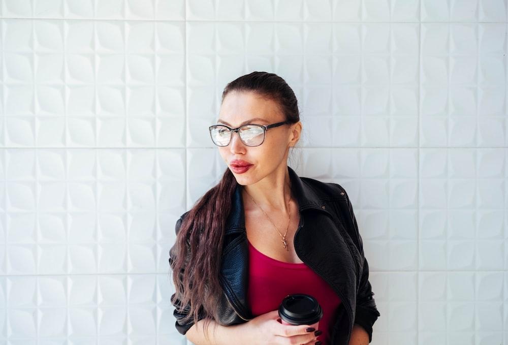 woman in black jacket standing near wall