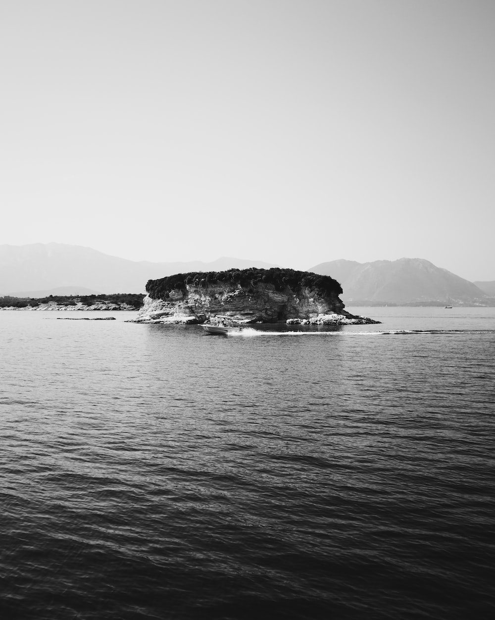 grayscale photography of boat near island during daytime