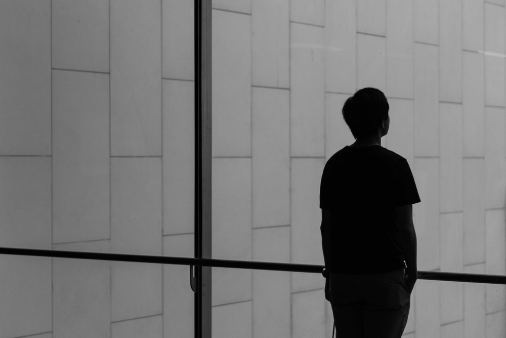 silhouette of a person facing glass wall