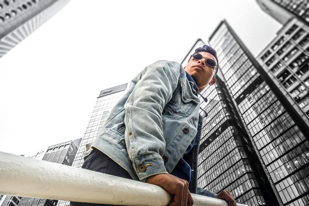 man standing near white steel post