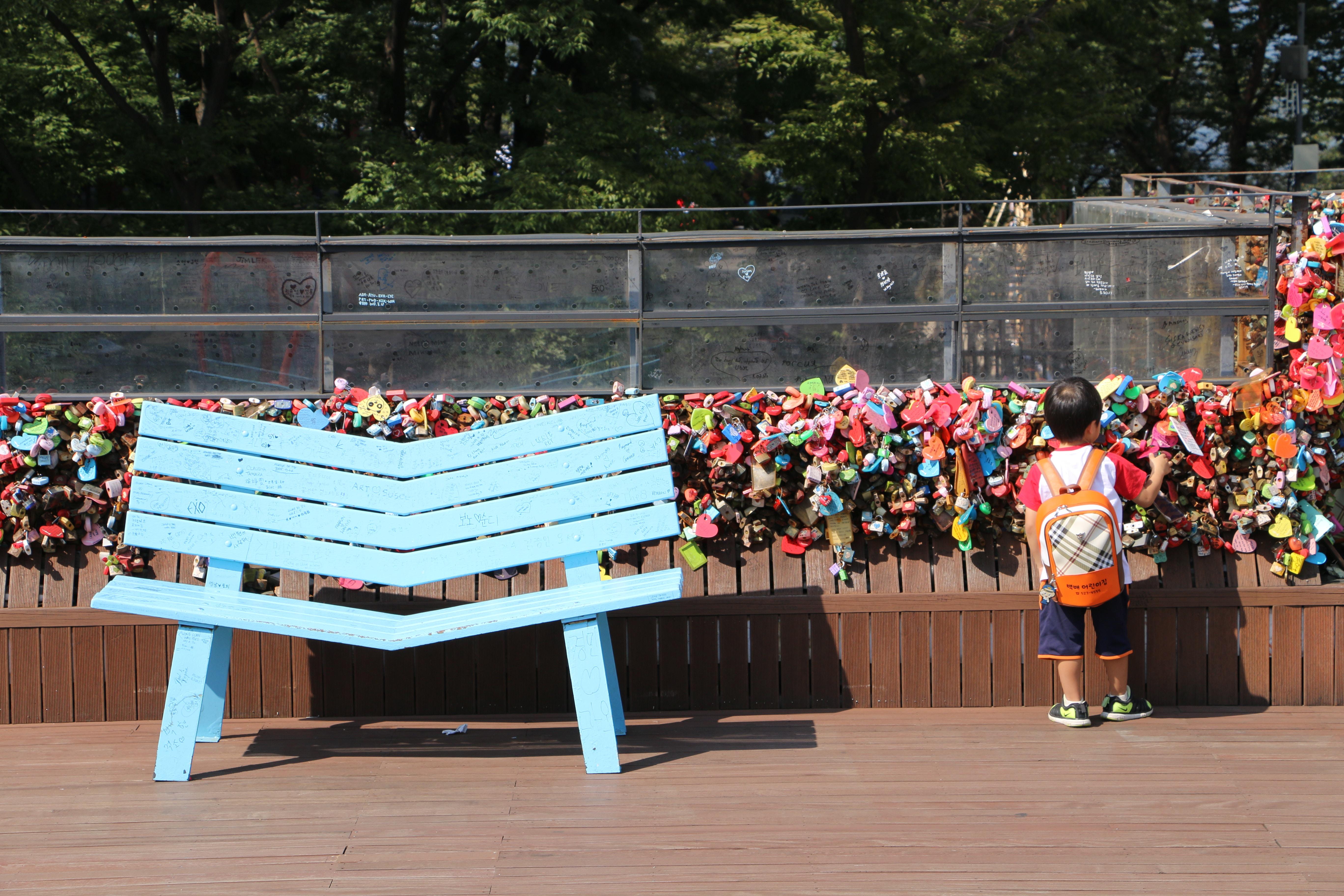 toddler standing near blue wooden bench