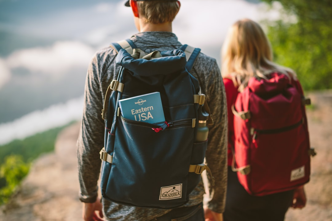 two man and woman carrying backpacks
