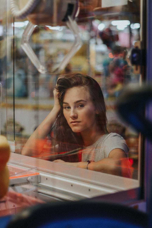 woman posing near arm arcade machine