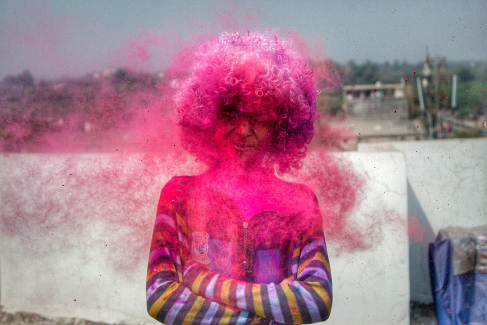 person having pink spray on hair during daytime