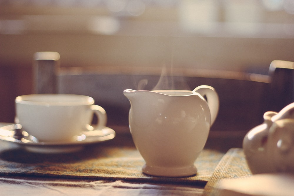 white ceramic teapot beside cup and saucer