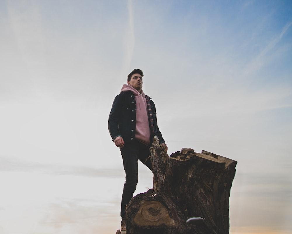 man in black jacket and pink pullover hoodie standing on tree log