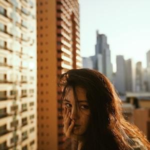 woman in gray top beside building