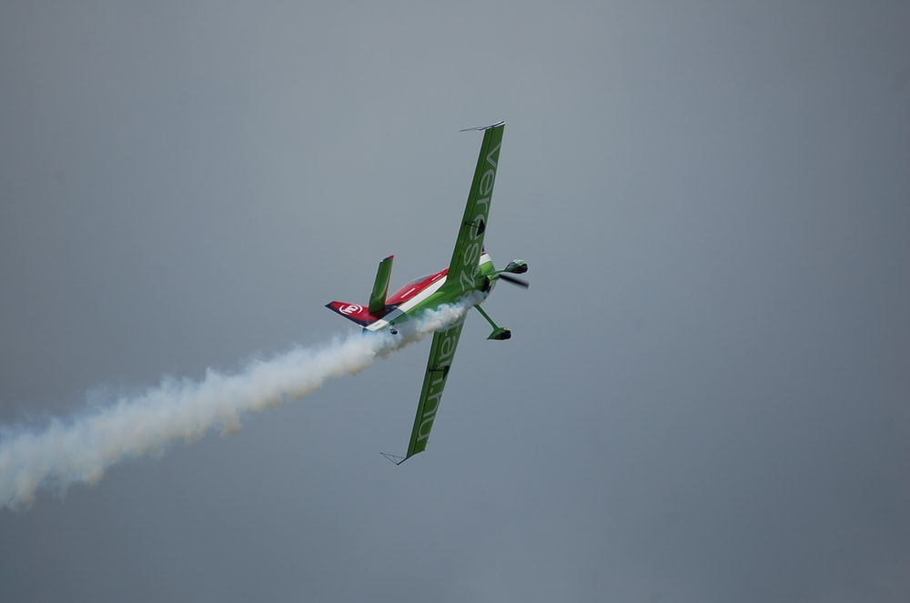green monoplane flying in the sky