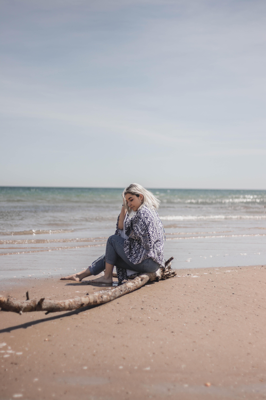 woman sitting on driftwood near shoreline