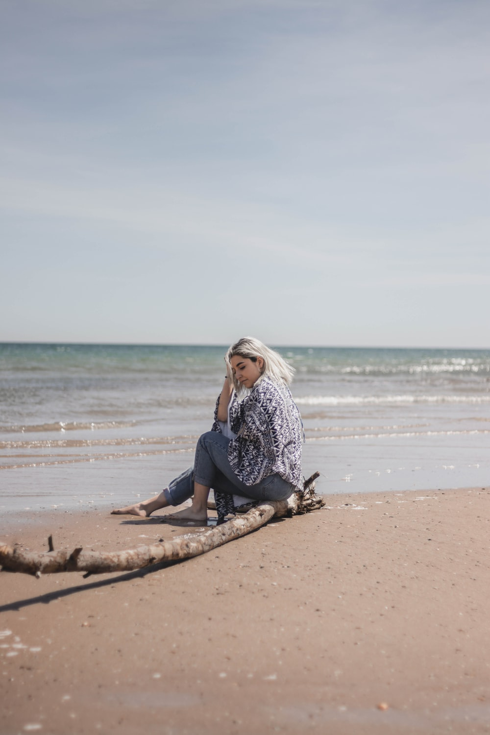 woman sitting on driftwood near shoreline