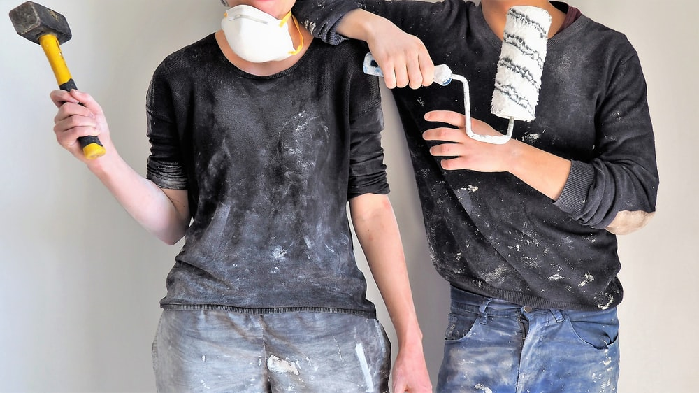 man and woman holding sledgehammer and paint roller