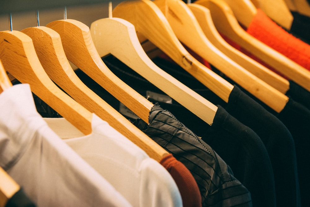 clothes hanged on brown wooden hanger
