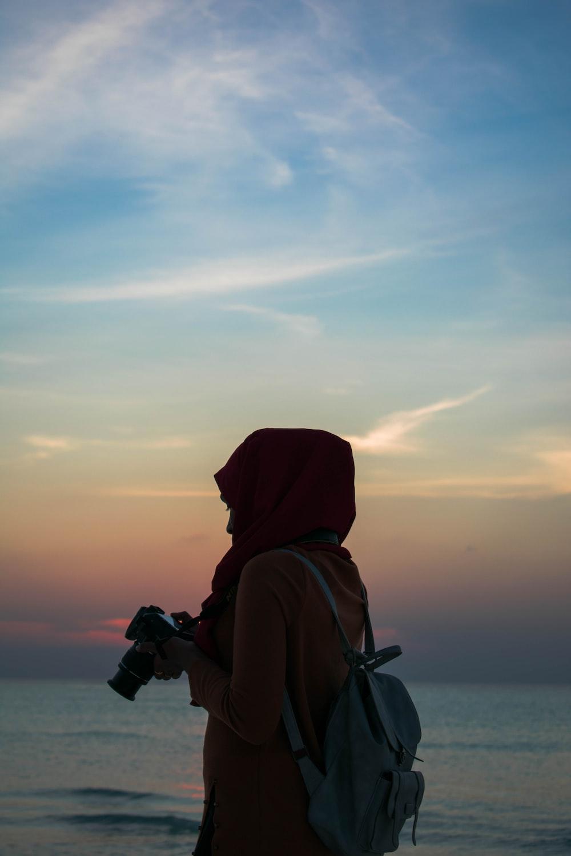 woman holding DSLR camera near body of water