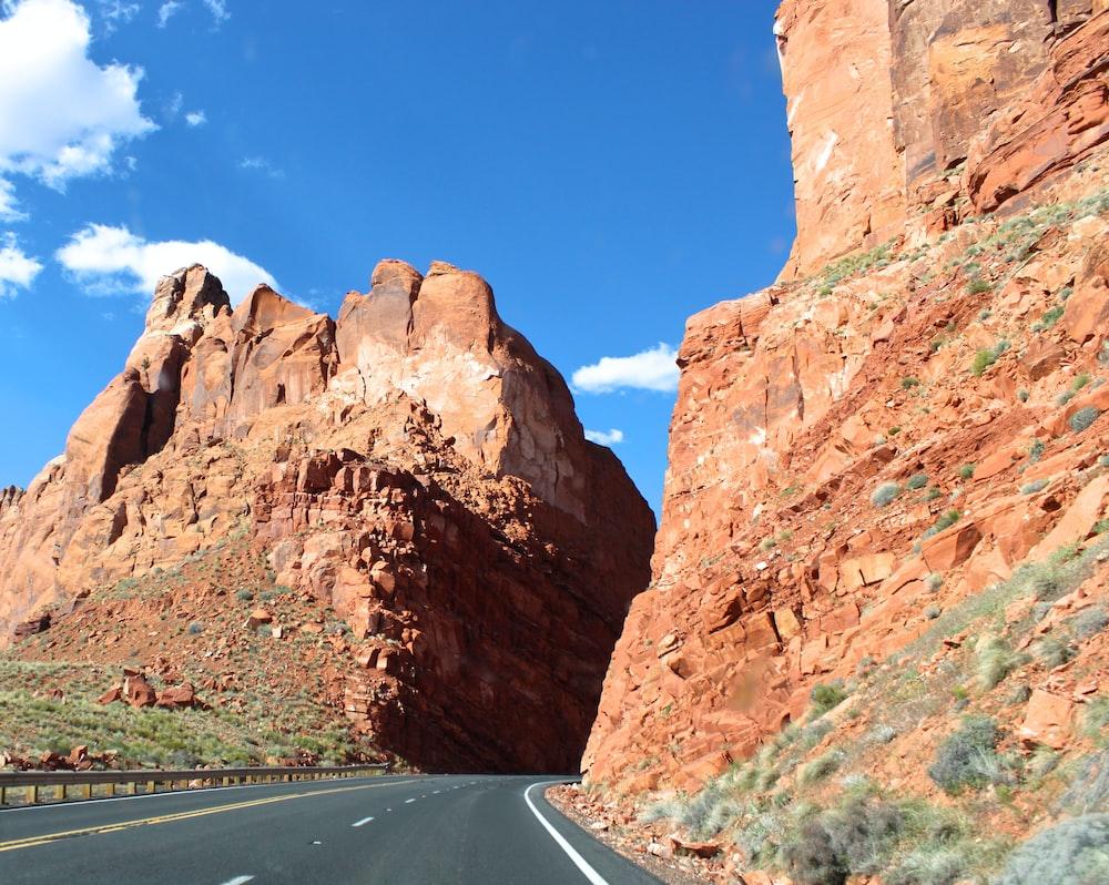 curved road in between brown rock cliffs