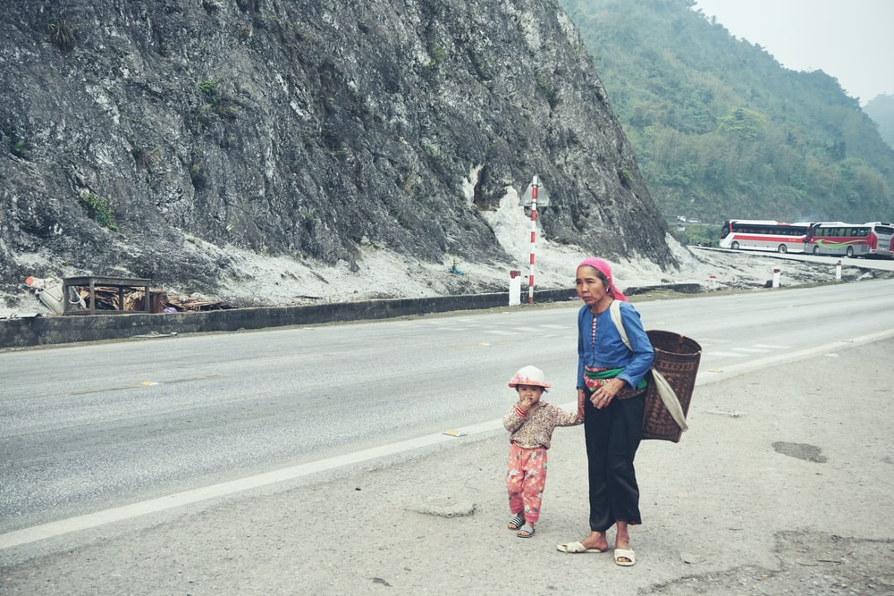 woman holding toddlers hand walking beside road