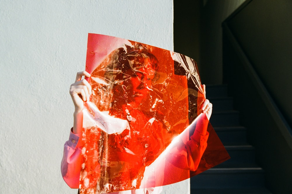 woman holding red film beside wall