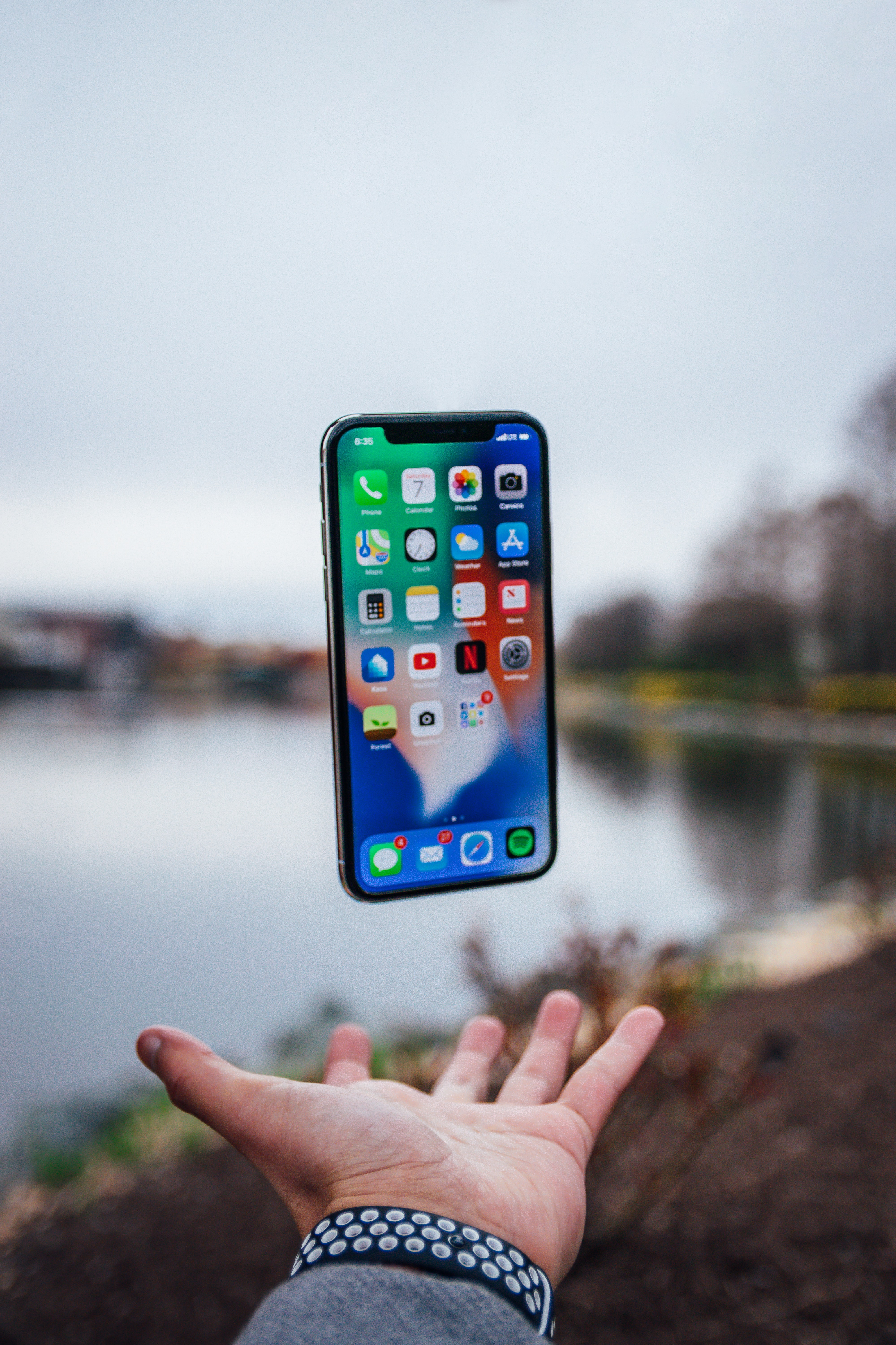 silver iPhone X floating over open palm