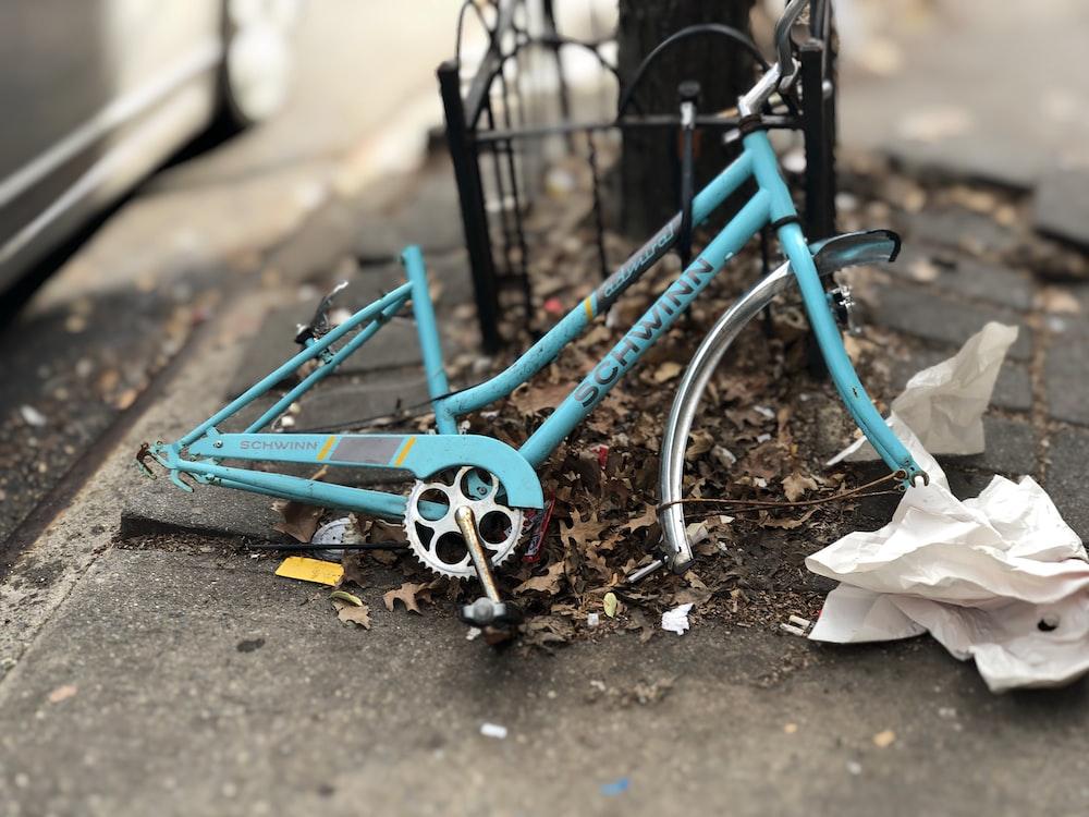 blue Schwinn bicycle frame leaning on black metal frame