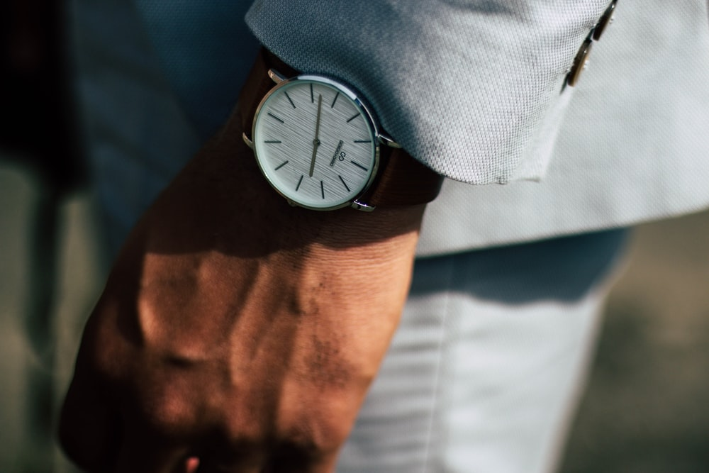 man wearing round analog watch and gray suit jacket