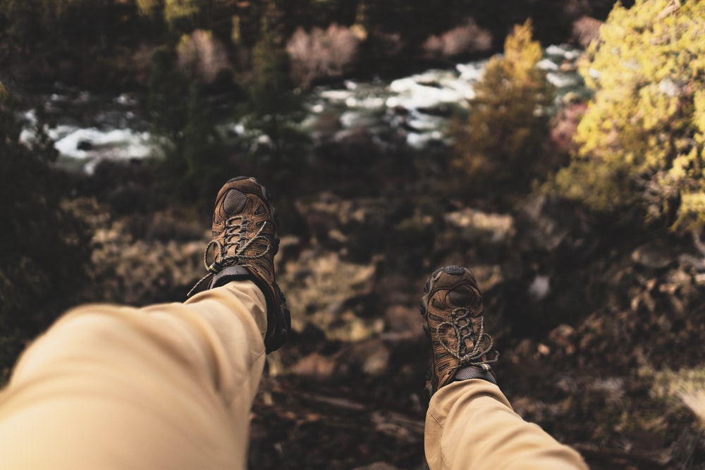 person wearing brown hiking boots sitting on cliff