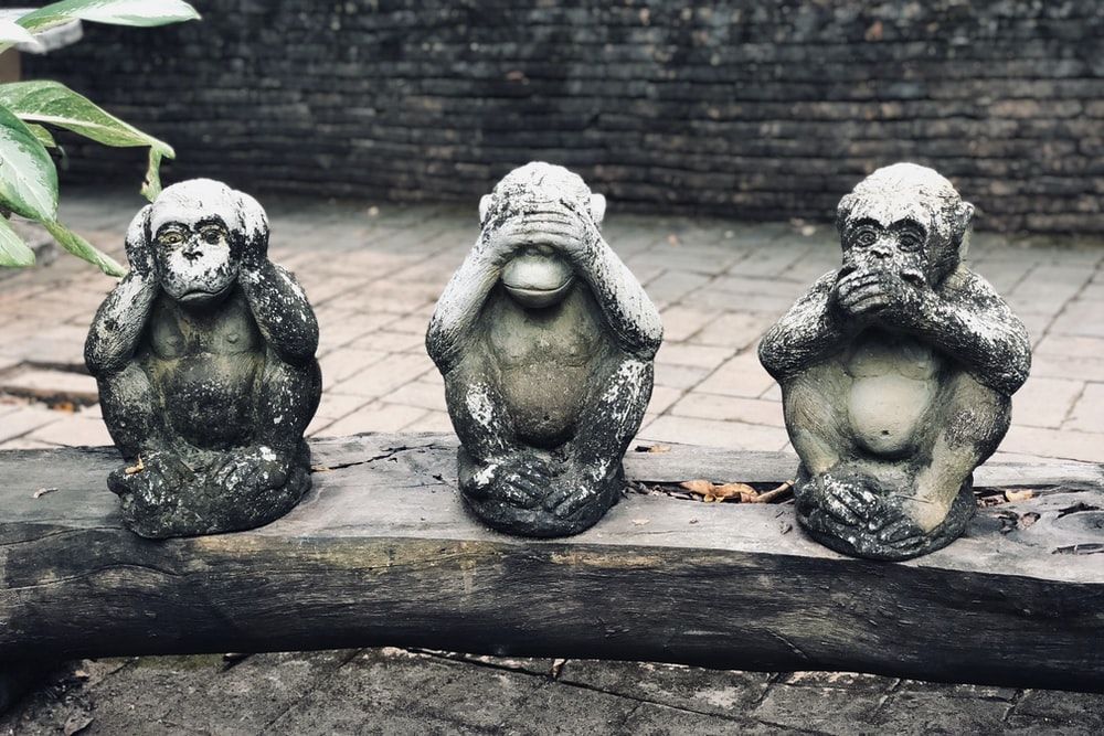 three wise monkeys statuette on log at daytime