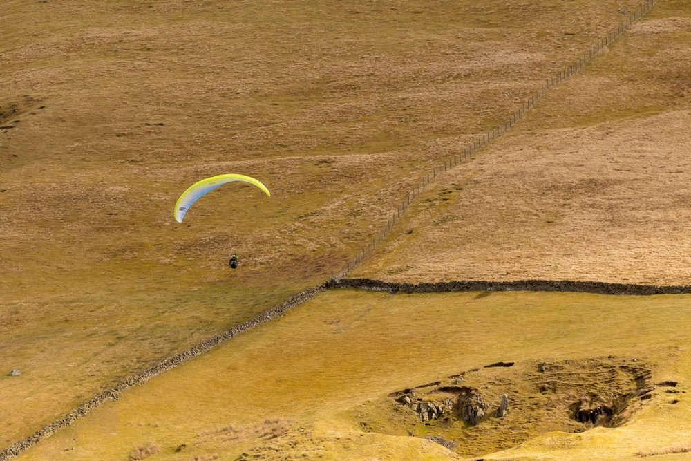 aerial photography of person gliding parachute