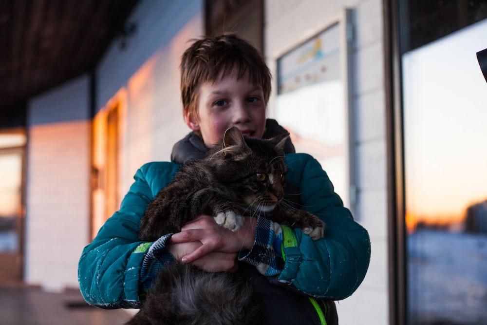 boy standing hugging cat