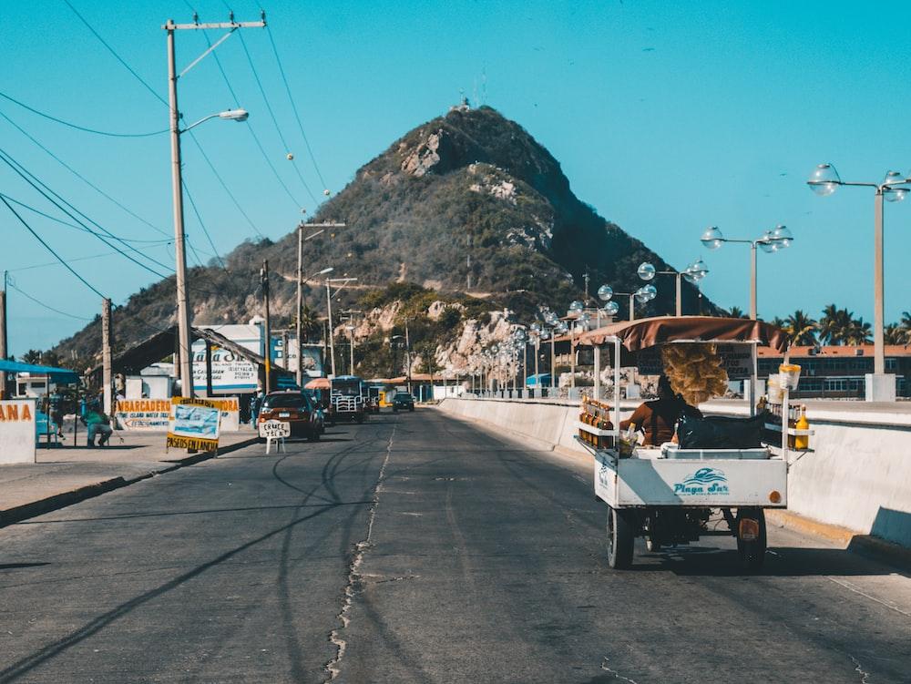 white auto rickshaw on riding on asphalt road towards green mountain