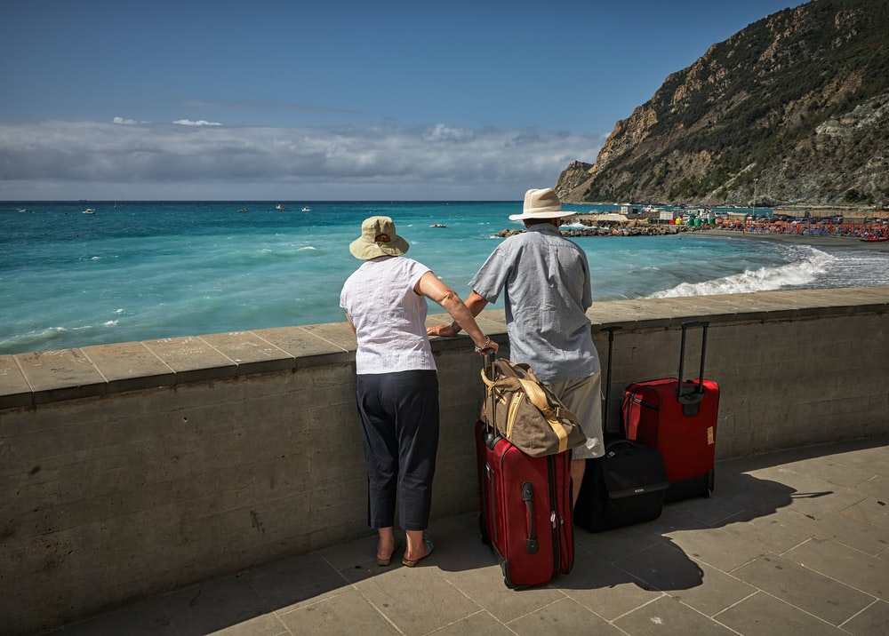 man and woman standing beside concrete seawall looking at beach