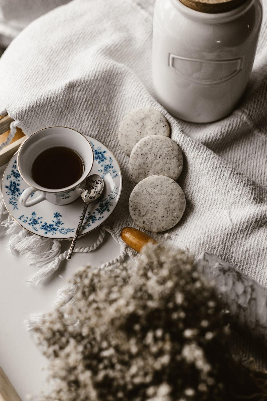 white ceramic mug fill with coffee on white saucer